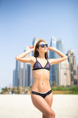 Young woman in bikini relax on the Dubai sea beach with skyscrapers on background. Summer vocation.