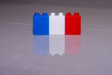 France flag (blue, white, and red) made of toy blocks on a tile with a reflection and space to add concept.