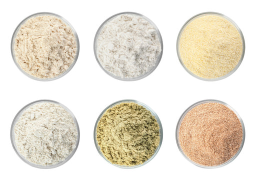 Set of organic flour in glass bowls on white background, top view