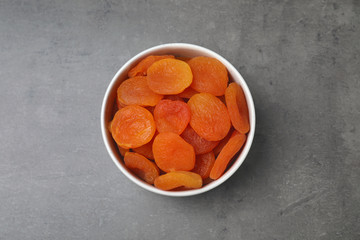 Bowl with dried apricots on grey background, top view. Healthy fruit