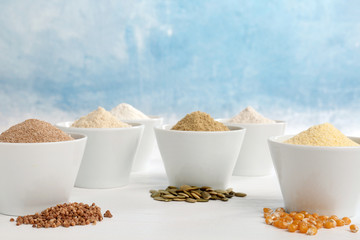 Bowls with different types of flour and seeds on table against color background. Space for text