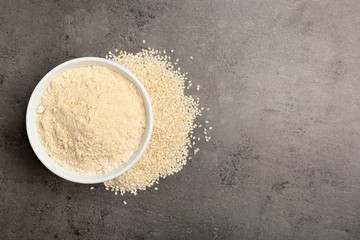 Bowl with sesame flour and seeds on grey background, top view. Space for text