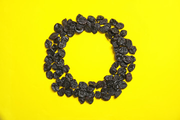 Frame made of tasty prunes on color background, top view with space for text. Dried fruit as healthy snack