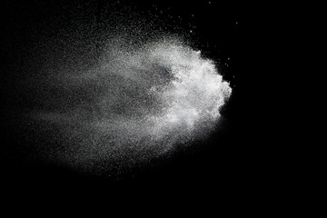 Bizarre forms of white powder explosion cloud against black background.White dust particles splash.