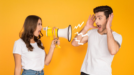 Woman shouting angrily at man with loudspeaker