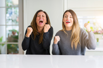 Beautiful family of mother and daughter together at home very happy and excited doing winner gesture with arms raised, smiling and screaming for success. Celebration concept.