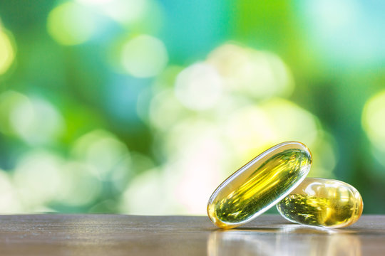 fish oil capsules on wooden table with natural background