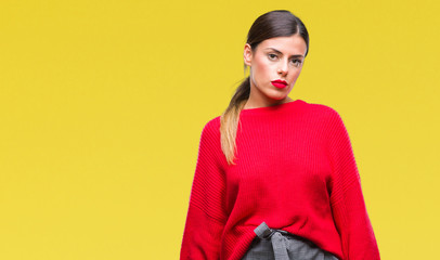 Young beautiful business woman wearing winter sweater over isolated background with serious expression on face. Simple and natural looking at the camera.