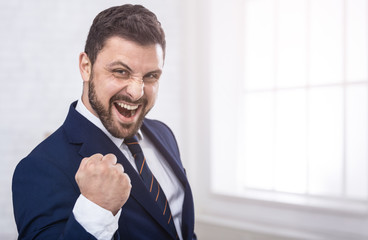 Businessman celebrating victory shouting happily in office