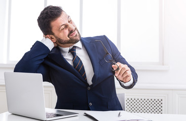 Feeling exhausted. Businessman working on laptop in office