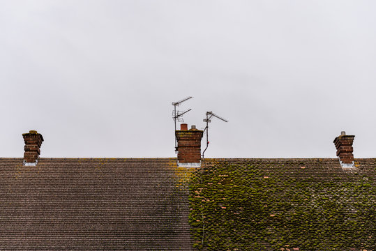 cloudy day view traditional british house roof with chimneys half full with moss and half cleaned