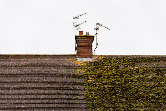 cloudy day view traditional british house roof with chimney half full with moss and half cleaned