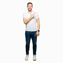 Handsome man wearing casual white t-shirt cheerful with a smile of face pointing with hand and finger up to the side with happy and natural expression on face