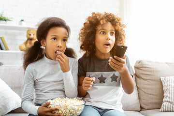 Little girls watching discovery channel and eating popcorn