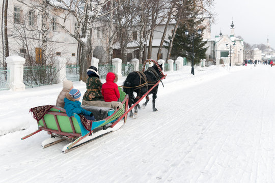 Winter holiday New Year's (Christmas) sleigh rides harnessed by horses (sledding) along the embankment of Veliky Ustyug