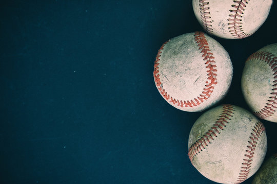 Old rugged group of baseballs on black background .  Baseball sports graphic with copy space.