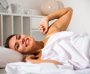 Woman in lingerie lying in bed
