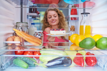 Woman taking gateau form fridge full of groceries. Unhealthy eating concept. Picture taken from the inside of fridge.