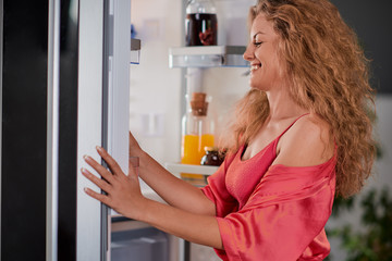 Woman taking food for breakfast from fridge full of groceries. Picture taken from the inside of fridge.