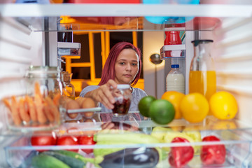 Woman standing in front of opened fridge  late at night and looking something to eat. Fridge full of groceries. Picture taken from the iside of fridge.