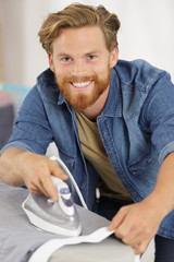 happy young man ironing at home