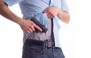 Man drawing concealed carry pistol