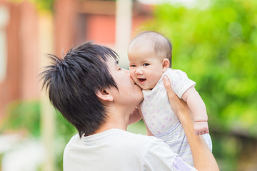 5 months baby feeling happy with her father in the garden.Portrait of Asian family.