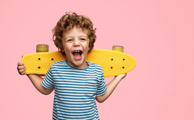 Cute boy with yellow skateboard Wall mural