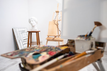 Interior of white studio of the artist, creative person. Easel, brushes, plaster head and figures. Attic, high ceilings.
