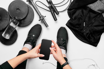 Young woman with mobile phone and sport equipment on white background flat lay top view. Fitness concept