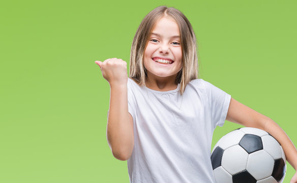 Young beautiful girl holding soccer football ball over isolated background screaming proud and celebrating victory and success very excited, cheering emotion