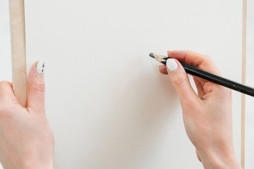 Woman artist's hand with a large simple pencil, draws on a clean white canvas, close-up.