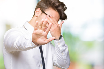 Young business man wearing glasses over isolated background covering eyes with hands and doing stop gesture with sad and fear expression. Embarrassed and negative concept.