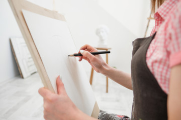 Young woman artist draws a pencil on canvas.