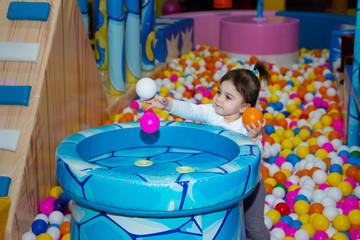 Toddler baby girl is playing with air blowing machine with plastic multicolored balls in indoor playground. ..shallow depth of field
