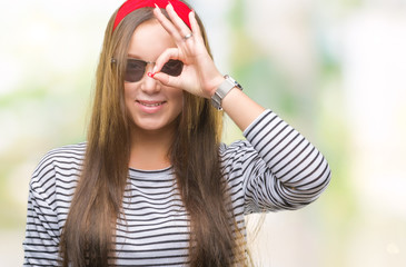 Young beautiful caucasian woman wearing sunglasses over isolated background doing ok gesture with hand smiling, eye looking through fingers with happy face.