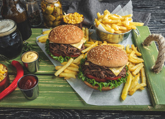 Wall Mural - Burger pulled beef barbeque , sandwich, french fries, sauce, dark beer, corn, on a wooden tray