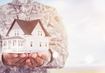 Miniature house in soldier hands