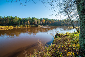 blue sky and clouds reflecting in calm water of river Gauja in latvia in autumn
