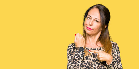 Beautiful middle age woman wearing leopard animal print dress In hurry pointing to watch time, impatience, upset and angry for deadline delay