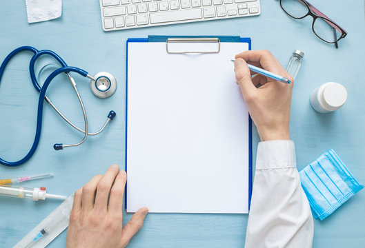 The top view of the doctor's hands is writing down a prescription or medical report on a blank sheet of paper. On the table are stethoscope and other attributes. Copy space.