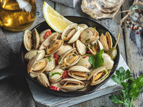 Cooked seafood clams in the iron pan portion with lemon and seasoning