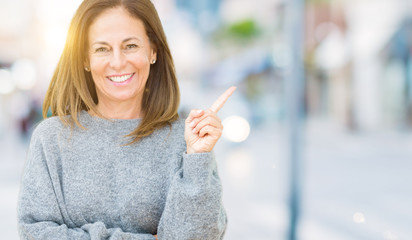 Wall Mural - Beautiful middle age woman wearing winter sweater over isolated background with a big smile on face, pointing with hand and finger to the side looking at the camera.