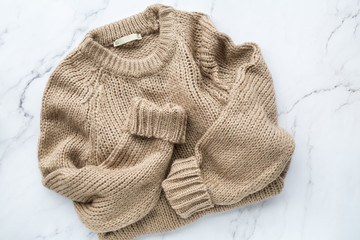 Female beige knitted sweater on white marble background top view flat lay. Fashion Lady Clothes Set Trendy Cozy Knit Jumper Autumn accessories. Female fashion look