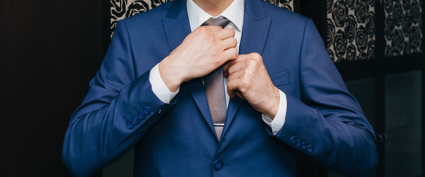 Groom is wearing the blue wedding suit. Stylish man is holding his tie in hands. Celebration day ceremony. Wedding fashion details.