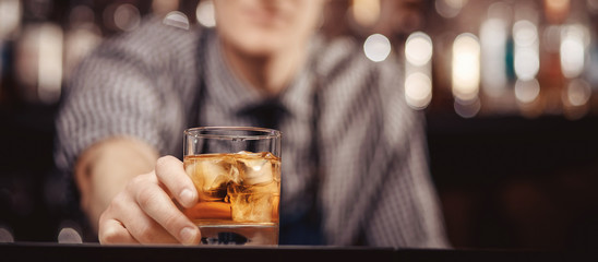 Papiers peints Alcool Barman holds out glass of whiskey with ice to male visitor. Concept rest in bar