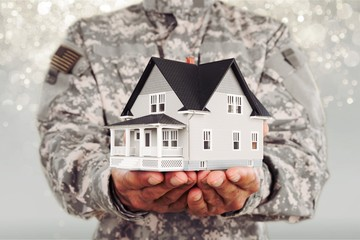 Miniature house in soldier hands, heroes, house under protection