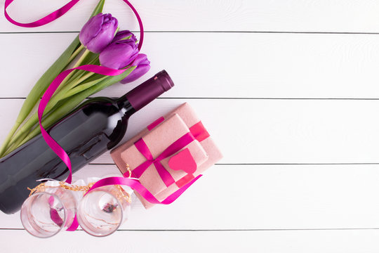 women's day. gifts with flowers and wine on white background