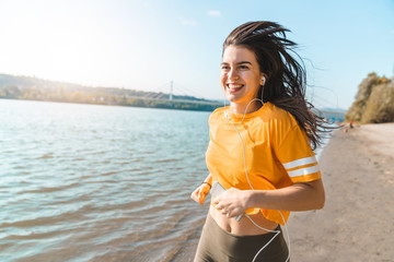 Young smiling fitness woman jogging on seaside while holding mobile phone and listening to music on a sunny day