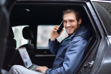 handsome businessman sitting in luxury limousine, working on laptop computer